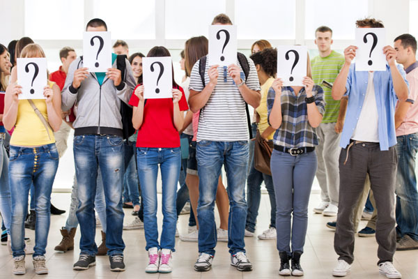 Group Of People Covering Faces With Question Mark Cards